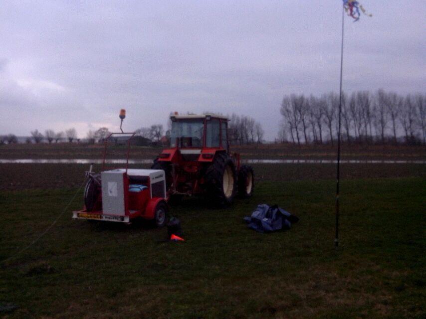 De liermachine aan de tractor in het veld