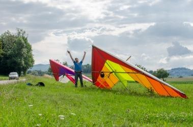 Paul staat naast zijn fleurige deltavlieger te juichen op het landingsterrein na een mooie vlucht