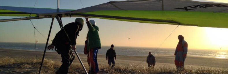Een piloot maakt zich klaar voor een start op een duin, bij het licht van de ondergaande zon