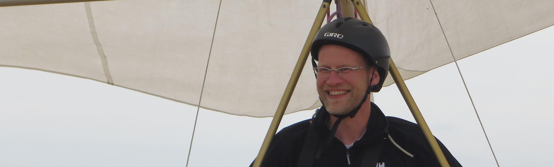 Een cursist loopt met zijn deltavlieger terug naar de start