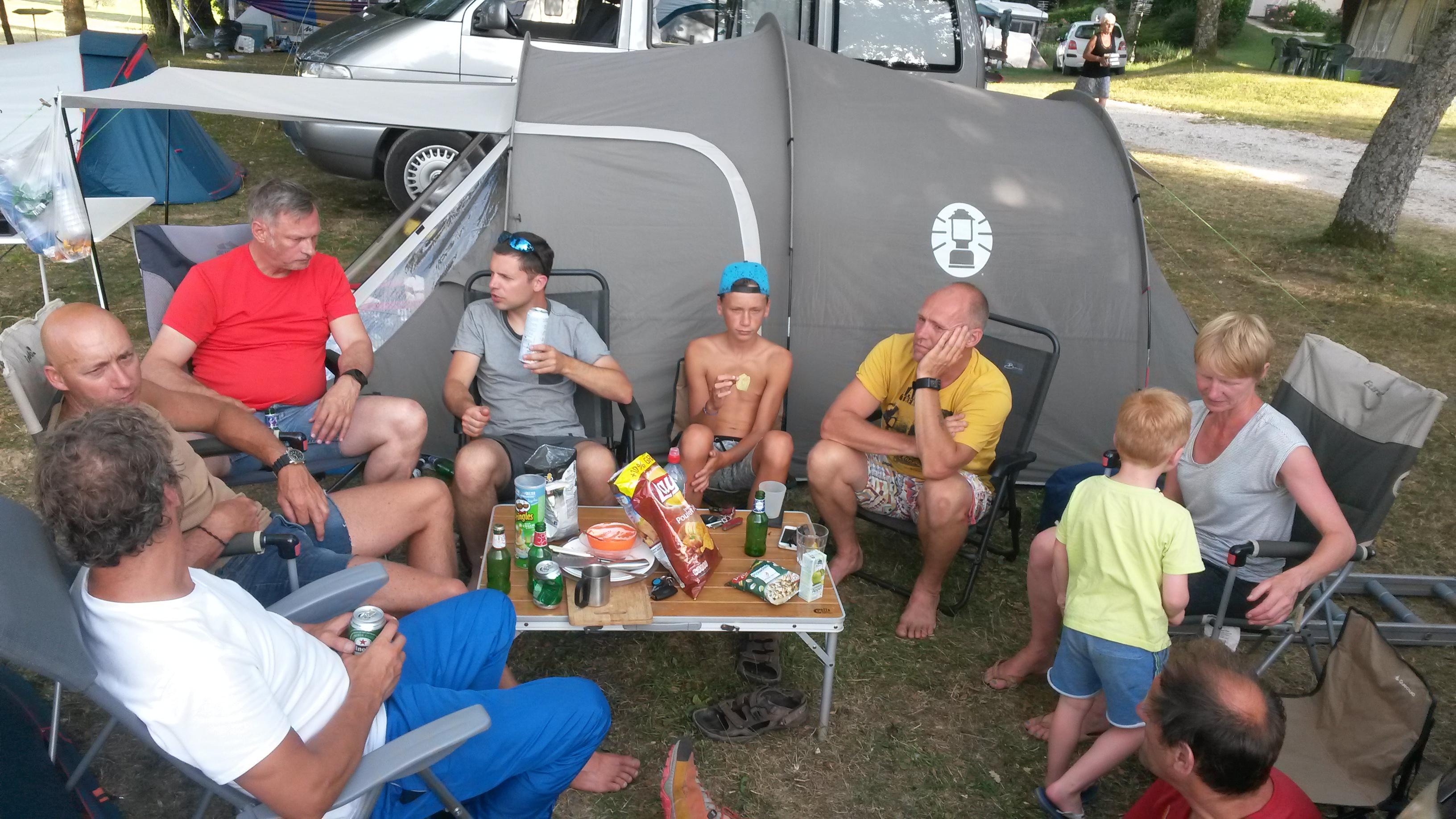 Een groep mensen op de camping rond een tafeltje met eten