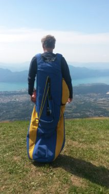 Een man met harnas voor deltavliegen aan op de rug gezien, uikijkend over een berglandschap