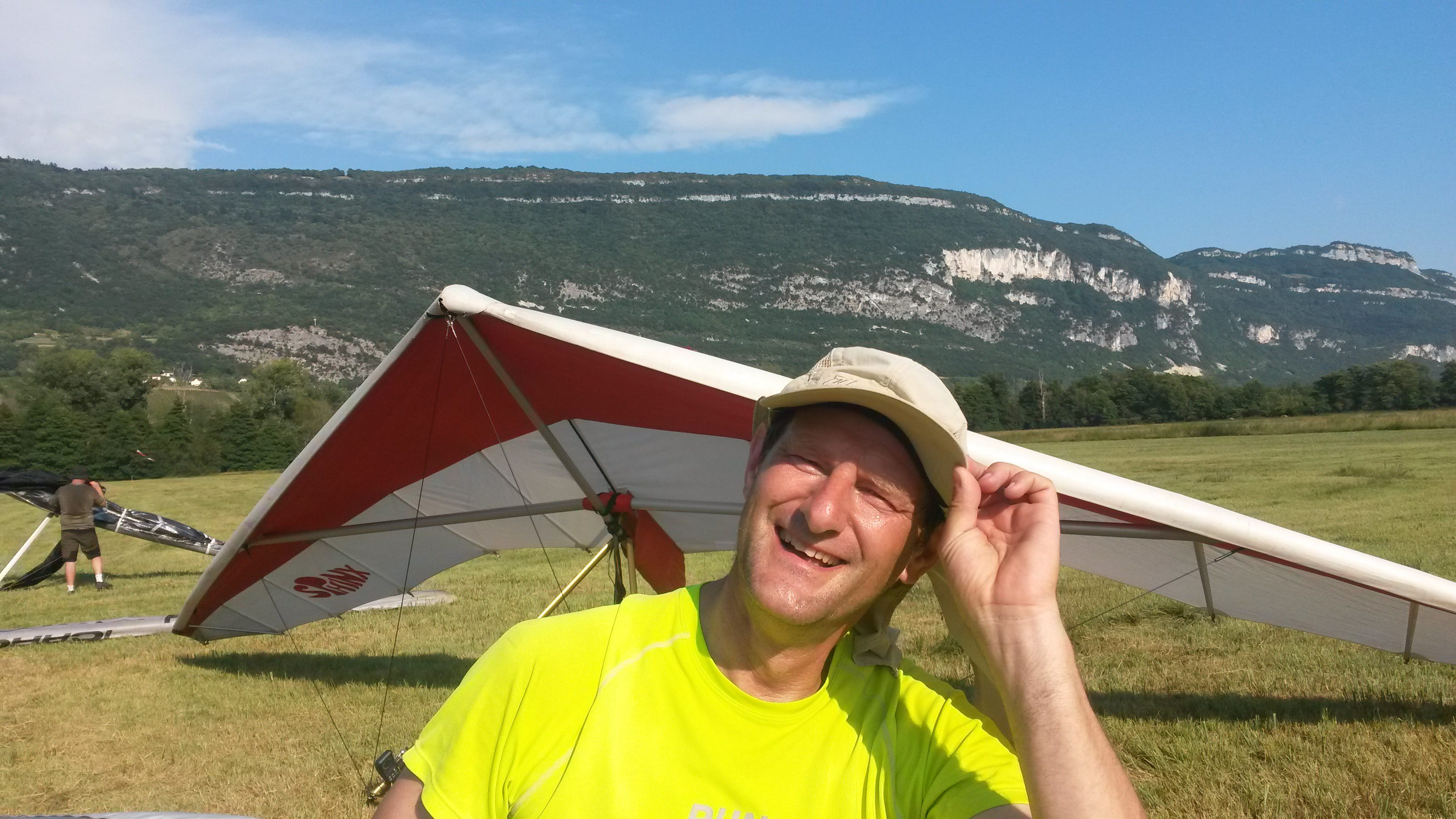 Man met pet op voorgrond, daarachter een deltavlieger op een groot veld. Op de achtergrond een berg en blauwe lucht
