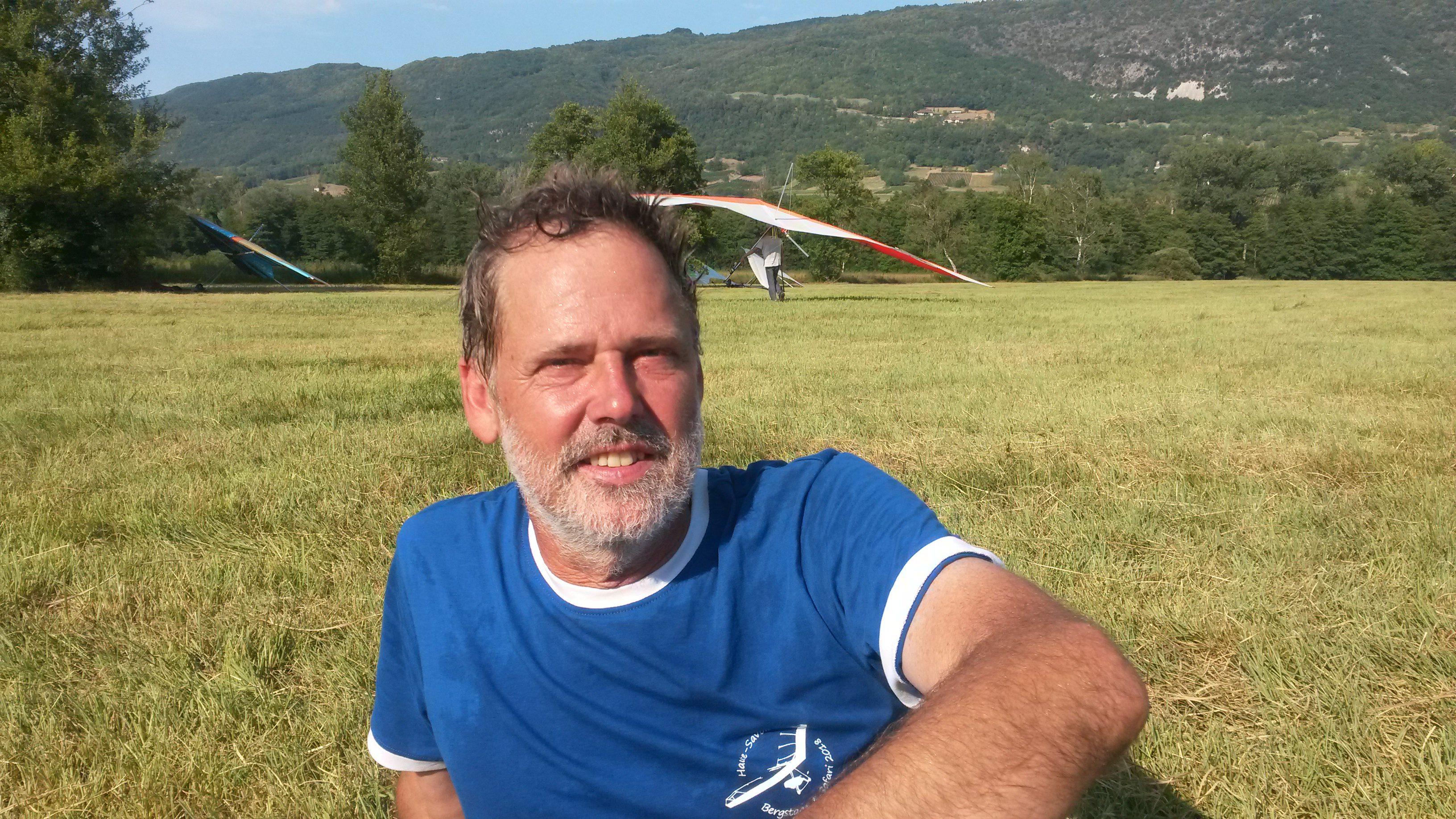 Foto van een man, zittend op een veld in de zon, met een landende deltavlieger op de achtergrond