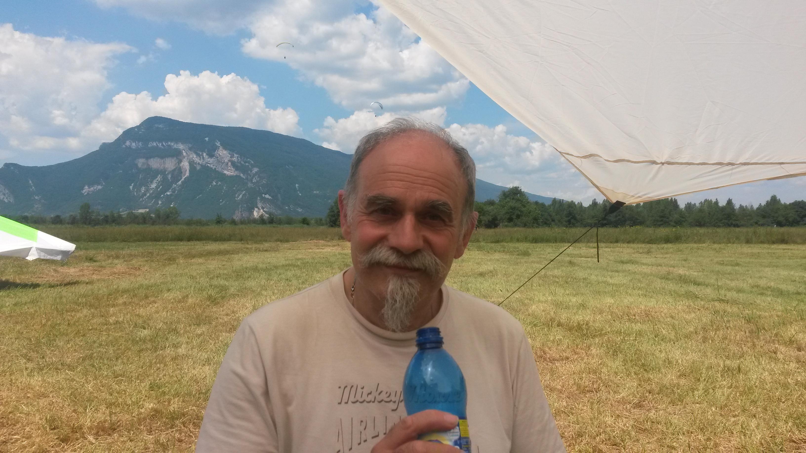 Portret van een man met een berg op de achtergrond en nog net een stukje deltavlieger in beeld. In de verte vliegen 2 paragliders