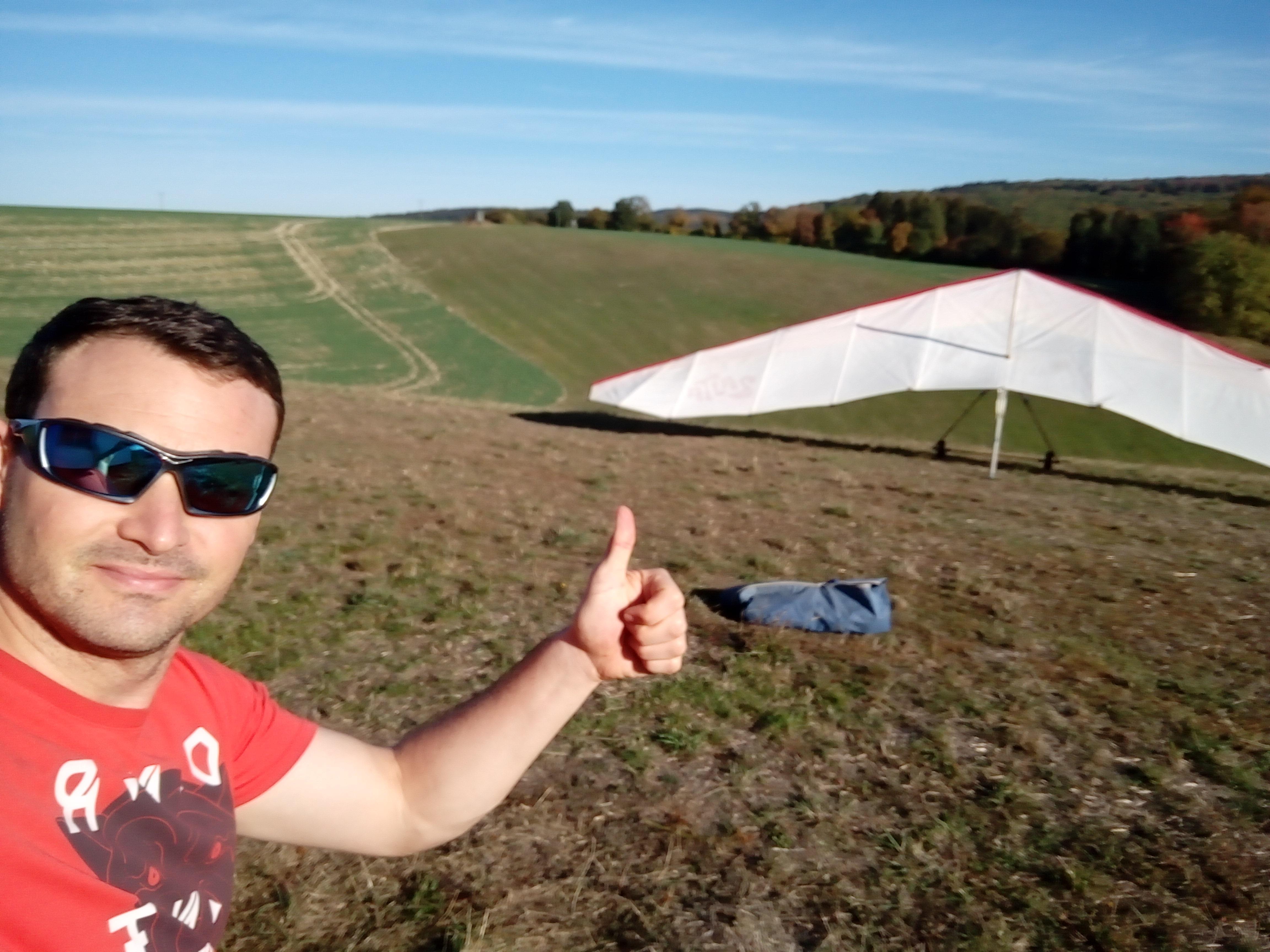 Selfie van man met zonnebril op, steekt zijn duim omhoog. Op de achtergrond een geparkeerde deltavlieger en een heuvellandschap