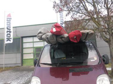 Randonaero-bus met 6 deltavliegers op het dak, voor de gevel van Bautek